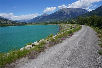 dirt road along the Serre Ponçon lake  in the mountains of southern Alps, France