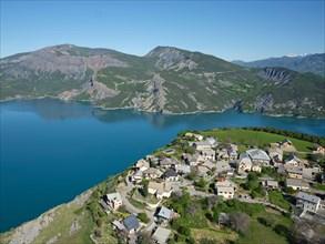 AERIAL VIEW - Village perched 250m-high above Lake Serre-Poncon. Le Sauze-du-Lac, Hautes Alpes, France.