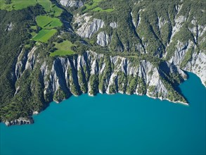AERIAL VIEW - Landscape of eroded ravines on the lakeshore of Lake Serre-Poncon. La Bréole, Alpes de Haute-Provence, France.