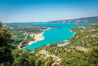 View of a turquoise lake and the surrounding forests