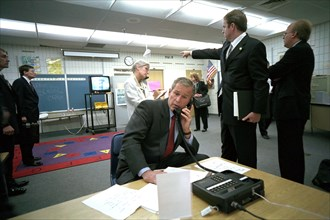 As Dan Bartlett, Deputy Assistant to the President, points to news footage of the World Trade Center Tuesday, Sept. 11, 2001, President George W. Bush gathers information about the terrorist attack fr...
