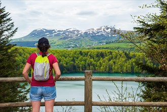 Young woman (unrecognizable back view) admiring view of lake Pavin in Auvergne Volcanic Regional Nature Park, France.  Active holidays in nature backg