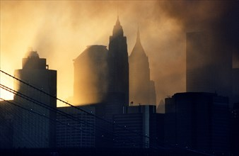 Sunset through the smoke of the WTC terrorist bombings of September 11 2001 frames the skyscrapers of lower Manhattan