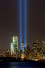 The twin beams of light of the Tribute in Light, an annual remembrance to the events of September 11, 2001, shine into the night sky in New York City on either side of the Statue of Liberty.