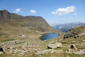 Low-angle shot on the Gentau Lake and the Ayous refuge (Pyrenees National Park - France). Le lac Gentau et le refuge d'Ayous.