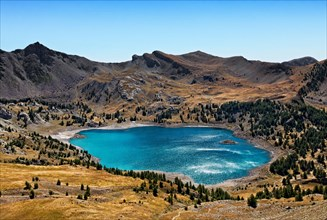 Image of Lac D'Allos (2228 m) during a windy day with sunlight reflections on the rippled water surface.