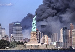 Sept. 11, 2001 - New York, New York, US - The Statue of Liberty stands against the backdrop of billowing clouds of smoke and debris over lower Manhattan after terrorists crashed two hijacked airliners...
