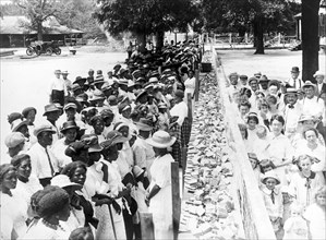 """Entitled: """"F.M. Gay's annual barbecue given on his plantation every year"""" shows crowds of African-American and white people separated by a long counter covered with slices of bread at a barbecue in Al..."""
