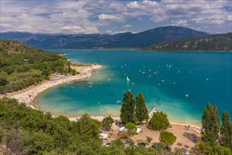 LAKE OF SAINTE-CROIX, PROVENCE, FRANCE - People on beach and in boats at man-made lake, lac de Sainte-Croix.