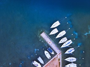 aerial view of boats parked near pier on the lake, blue water landscape from drone