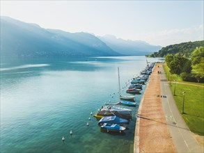 aerial landscape of Annecy lake, Alps, France, yachts and sailing boats from above, pedestrian walk near crystal blue water