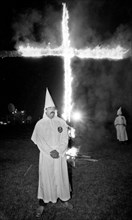 A Member of the KKK stands next to cross lighting in Rumford Me during rally in the small town Maine town. The Klan had been active in Maine in the 1920's and 30's , This group of Klansmen openly invi...