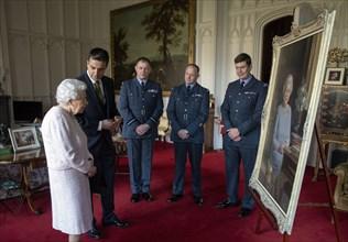 La reine Elisabeth II observant un nouveau portrait d'elle au château de Windsor