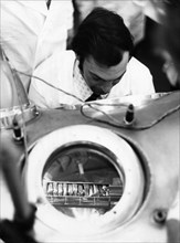 The ampule containing lunar soil and rock delivered by the re-entry module of the soviet lunar lander, luna 24, is being examined in a vacuum chamber by a scientist, it has been opened at the receivin...
