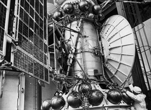 A technician with a working model of the venera 15 and 16 soviet space probe which is to be used for tests, 1982.