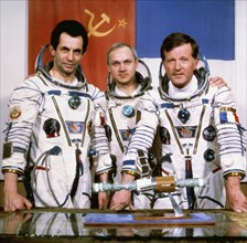 Salyut 7, soyuz t-6, cosmonauts aleksandr ivanchenkov, vladimir dzhanibekov, and jean-loup chrétien (france) pose with a model of the salyut 7 and soyuz spacecraft, 1982.