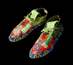 Pair of quilted mocassins decorated with beadwork and quillwork in a design of bear claws and buffalo heads