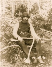 Bearded man armed with ax, rifle, hunting knife, and two pistols 1886