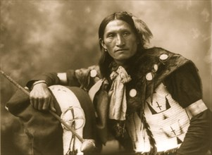 Eddie Plenty Holes, a Sioux Indian, half-length portrait, facing front, holding tomahawk 1899