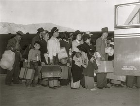 Japanese-Americans transferring from train to bus  bound for war relocation authority center at Manzanar 1942