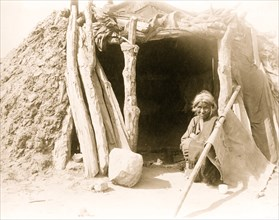 Old Navajo Indian seated in doorway of hogan 1901