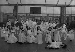 The dance of the Children of the Sunshine with Ellen sleeping in the foreground. Miss Mackay's Pageant Children of Sunshine and Shadow as presented at Washington Irving High School. 1916