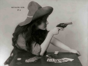 Young Cowgirl Hold Pistol Over a table of Playing Cards 1912