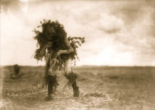 Yebichai, the beggar, Tonenili-Navajo Indian, dressed in spruce branches 1904