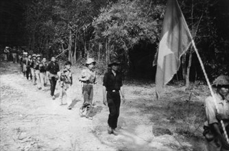 South vietnamese guerrillas file through the jungle along the ho chi minh trail, the flag with a yellow star on a red and blue background is always carried into battle, vietnam war, mid 1960s.