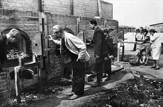 Lublin murder camp [,,,] the batteries of inciner-[,,,]at disposed of the bodies  lublin, poland lublin residents examine victims' remains in ovens of madjanek concentration camp.