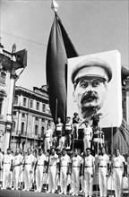 Participants in the annual physiacal culture parade standing under a portrait of joseph stalin near red square in moscow, ussr, 1930s.