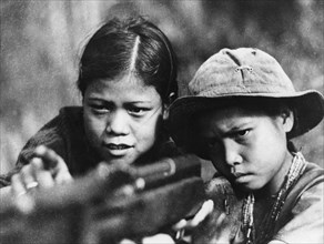 A fourteen year old viet cong girl teaching her younger brother to fire a rifle, thua thien province, south vietnam, 1968, vietnam war.