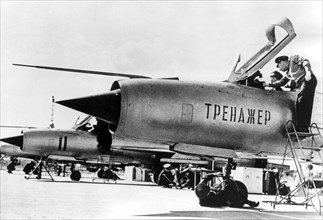 September 1966: a north vietnamese student pilot in a non-flying mig-21 fighter jet trainer, with him is his soviet flight instructor, lettering on fusilage: 'trainer'.