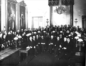 Petrograd, russsia 1917: first members of the provisional government in the state council chamber, alexander kerensky standing second from right (of faces not in shadow) .