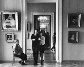 A young russian couple walk through the halls of a moscow museum, art gallery, ussr, 1960s.