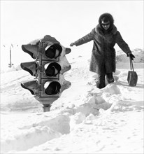 A woman walking by a traffic light on a huge snow drift after a five-day blizzard in yuzhno-sakhalinsk in the southern part of the soviet island of sakhalin, february 1970.
