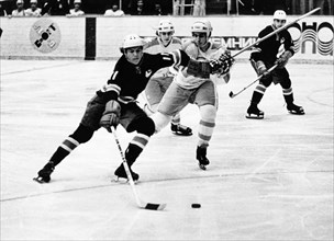 A juniors hockey match between the soviet army team of leningrad and the verdun maple leafs of canada, s, vasilyev (left) fighting for the puck, f, bernard (center) and v, pribylov (right), march 1974...