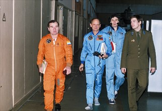 American astronauts bonnie dunbar, norman thagard, v, dezhurov, and us ambassador thomas pickering (bent) during survival training prior to the soyuz tm-21 mission to the mir space station, 1995.