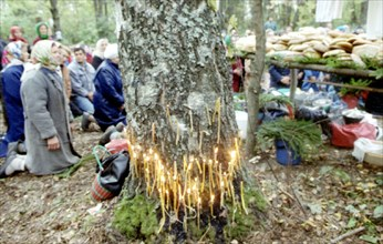 The republic of mari el (russian federation), pagans pray in the sacred kupriyanovskaya grove during a pagan holiday before sharing a common meal of boiled meat and bread, 11/95 .