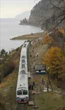 Irkutsk region, russia, commuter train stops at a station of the circular railway running along lake baikal shore, this is an old stretch of the trans-siberian railroad, november 2006.