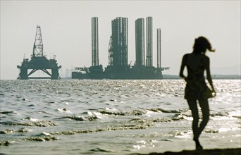 A woman in silhouette walking along shikhov beach on the shore of the caspian sea with an off-shore oil rig under construction in the background, baku, azerbaijan, october 2002.