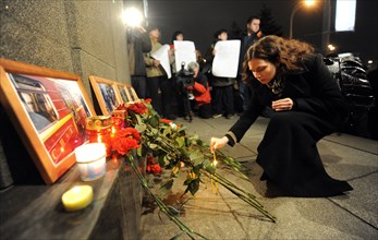 Moscow, russia, march 30, 2010, a woman lights candles to commemorate victims of the metro bomb explosions, blasts rocked two stations on sokolnicheskaya line of the moscow underground during the rush...
