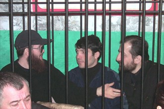 Makhachkala, dagestan, russia, december 5, 2001, salman raduyev (left) and his supporters on terrorism charges pictured on wednesday behind the bars at the courtroom, after witnesses and survivors of ...