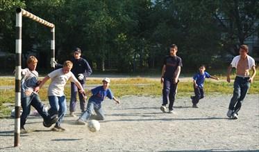 Teenagers play football in a chelyabinsk yard, russia, august 2006.