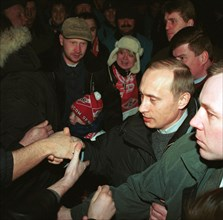 Acting president and prime minister vladimir putin (2nd from right) being greeted by football fans at moscow's luzhniki stadium on saturday when he came to watch a match between spartak moscow and ala...