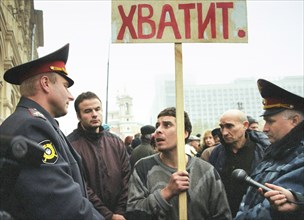 Moscow,russia, october 25 2002: policemen trying to pursuade a demonstrator with a slogan 'enough' in hand to stop his unauthorized protest action during the meeting which was organized by relatives o...