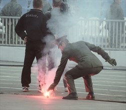Moscow, russia, april 20, 2003, a firefighter putting out a smoke candle during a russian championship's soccer match cska (moscow) vs rostov (rostov-on-don), on saturday, rosrov won 1:0.