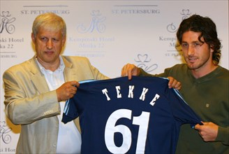 St, petersburg, russia, august 2, 2006, fc zenit president sergei fursenko, left, and turkish national team forward fatih tekke hold a soccer shirt bearing the number 61 and tekke's name as they pose ...