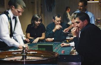 Gamblers at a roulette table ina casino in bashkiria, russia, 2001.