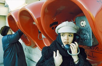 Fashionable young woman at the public phones in lipetsk which have been free since 1996, april 2001.